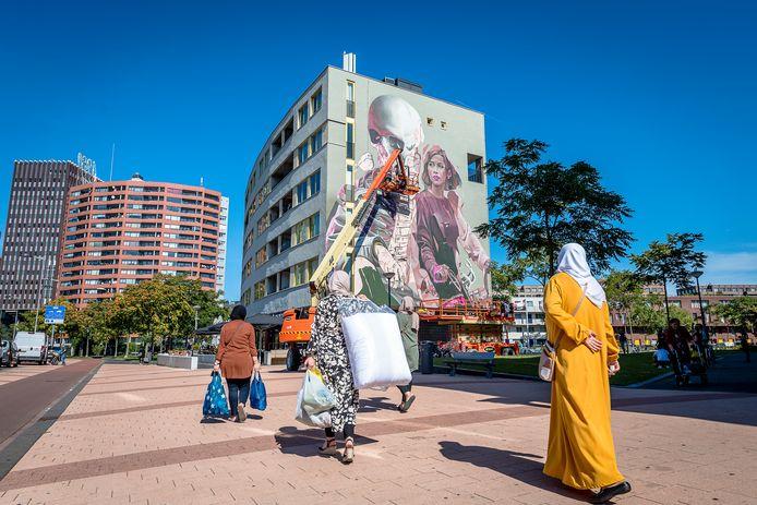 Vrouwen lopen voorbij aan de muurschildering die het Rotterdams/Amsterdamse duo Telmo Miel maakte in samenwerking met Smug.