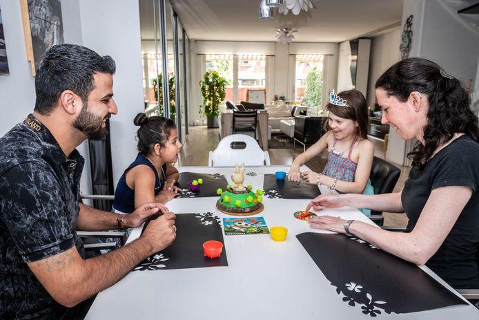 Buurtgezinnen is een maatschappelijk initiatief met als basisgedachte: opvoeden doen we samen. Abdulaziz Khaled met zijn dochter Watfa, Sonja van Schendel en haar dochter Megan spelen graag samen het konijnenspel.