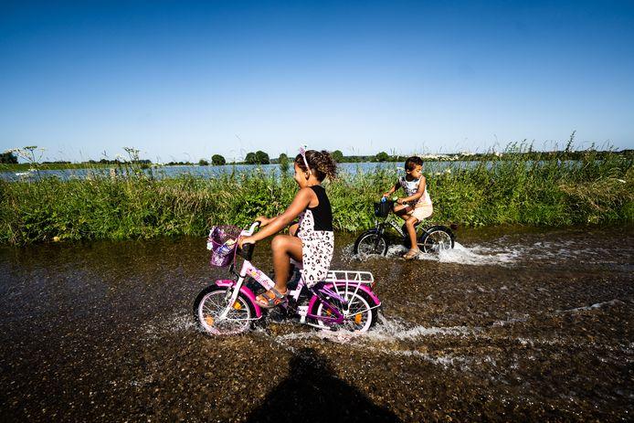 Hoogwater in Heteren. Lennox (6) en Djadja (4) spelen met de fiets in de uiterwaarde.