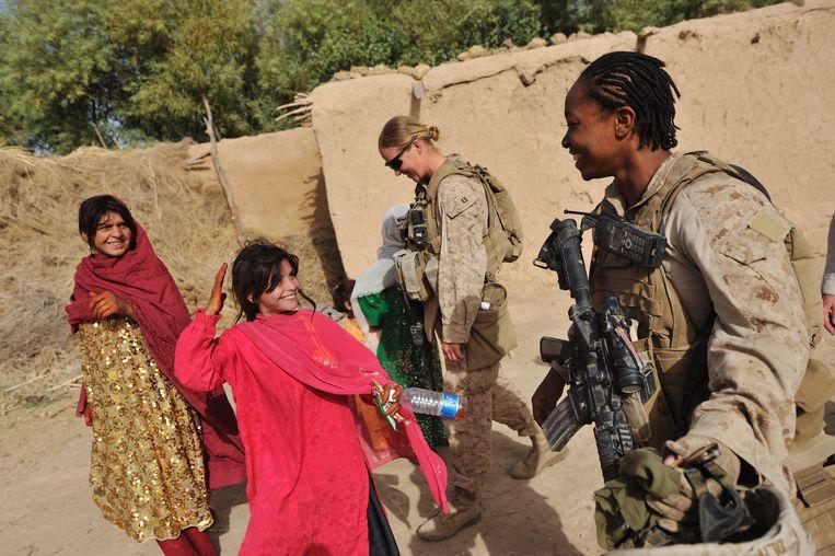 Amerikaanse mariniers nemen even hun helm af om twee meisjes te tonen dat ze vrouwen zijn. Beeld © Lynsey Addario / 2021 The Atlantic Monthly Group, Inc.   All rights reserved. Distributed by Tribune Content Agency