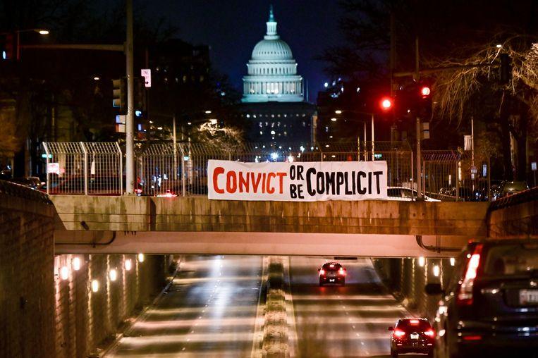 Een spandoek met  'veroordeel of wees verantwoordelijk' hangt boven een viaduct in Washington D.C., met op de achtergrond het Capitool. Beeld REUTERS