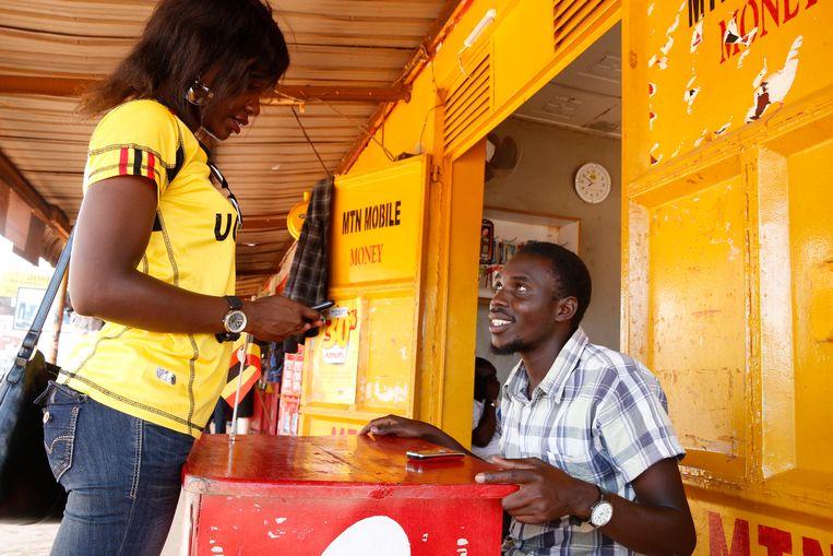 Een klant verstuurt geld met haar mobiele telefoon in Oeganda. Beeld Getty
