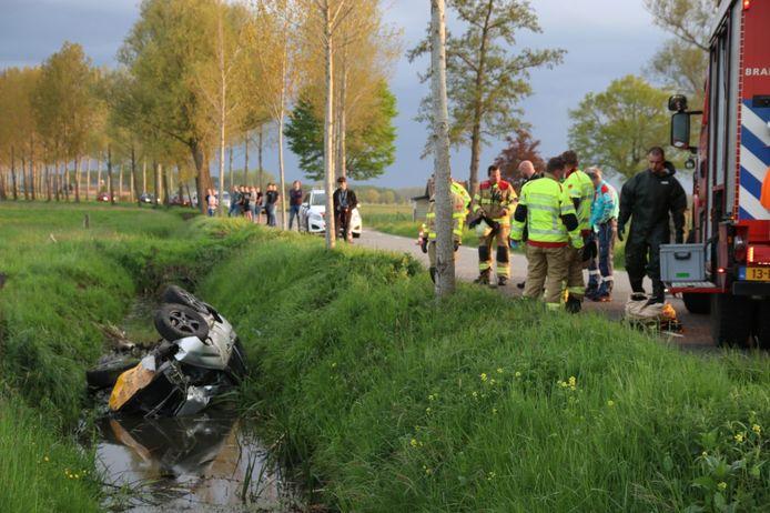 De auto die zonder inzittenden zwaar beschadigd in een sloot op zijn kant ligt.