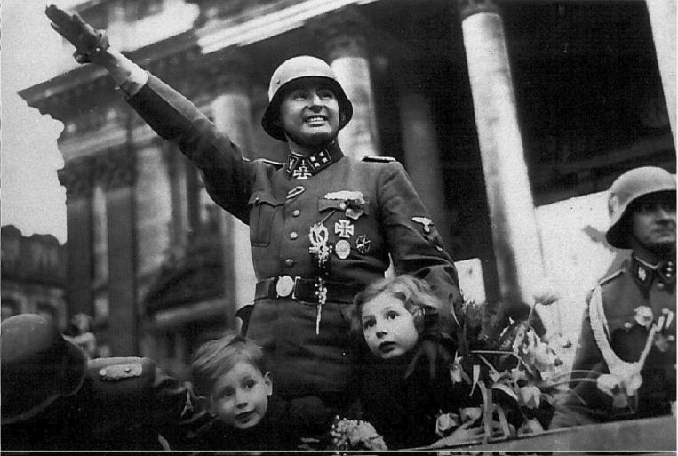 Degrelle keert in 1944 met het Waals Legioen terug in België en groet de Brusselaars. Beeld BELGA