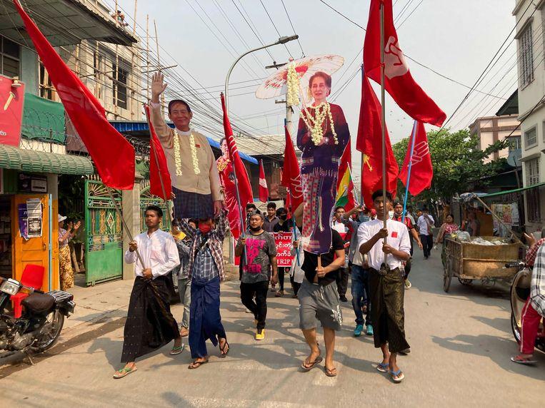 Demonstranten in Mandalay dragen maandag een foto van ex-regeringsleider Aung San Suu Kyi (rechts). Beeld AP