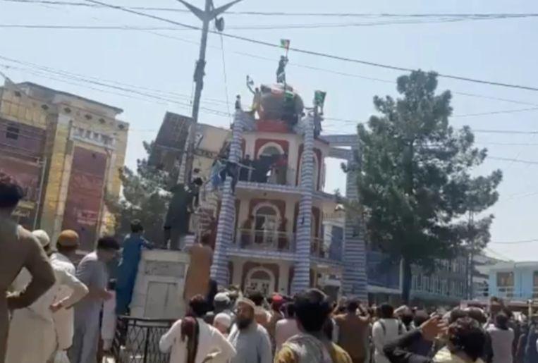 Bovenop een toren in Jalalabad wordt een vlag vervangen. Beeld Twitter/@bsarwary