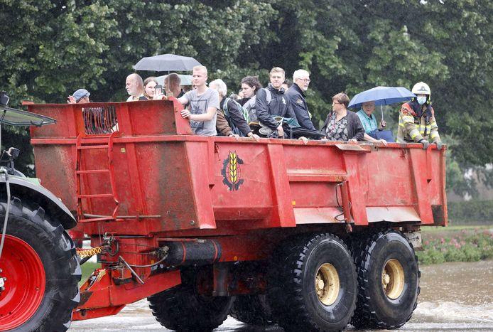 De brandweer helpt met de evacuatie van mensen uit hun woningen door de wateroverlast in Zuid-Limburg. Door het almaar stijgende hoge water als gevolg van de de overstroming van de Geul zijn straten ondergelopen.
