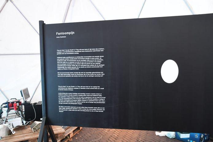 Passerende bezoekers zien de achterkant van het kunstwerk