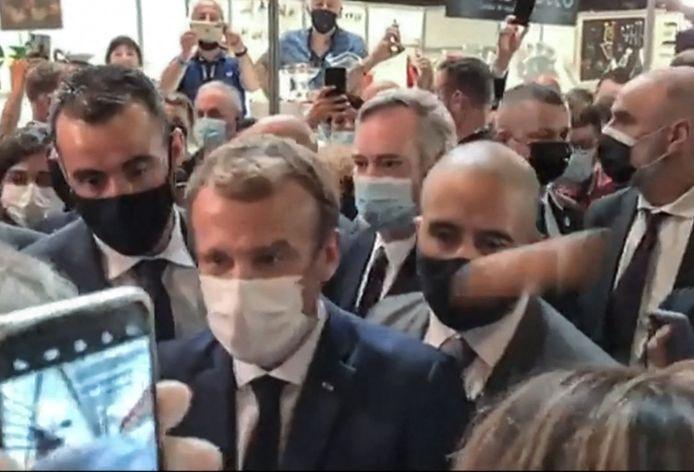 Het eitje ketste van de linkerschouder van Macron.