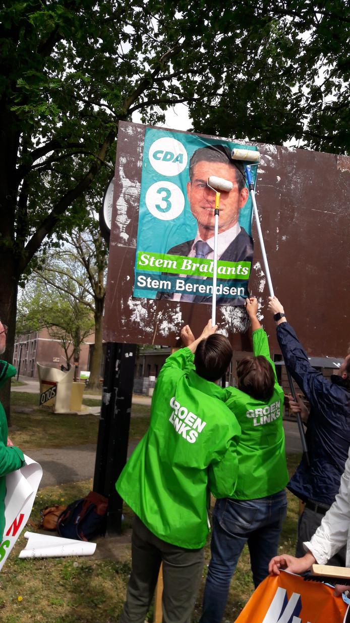 Leden van GroenLinks Oss plakken met toewijding een poster van het CDA.