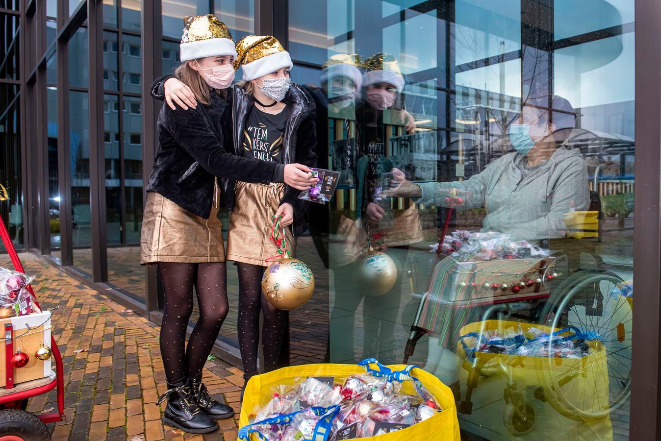 De meiden mogen niet naar binnen, maar patiënt Annie van den Berg uit Dordrecht neemt het cadeau graag aan.