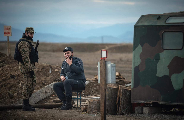 Een agent in gesprek met een militair bij een militaire post vlakbij de verwoeste stad Agdam in Nagorno-Karabach. Beeld Freek van den Bergh / de Volkskrant