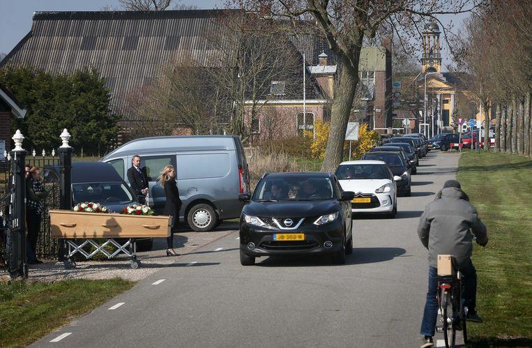 Nabestaanden nemen vanuit de auto afscheid van een overledene. Wegens de coronacrisis zijn er niet meer dan 30 mensen welkom bij begrafenissen. Beeld ANP