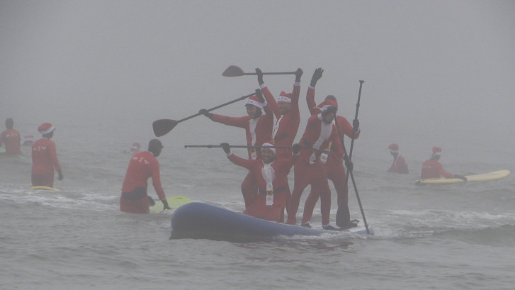 Surfende kerstmannen aan het Scheveningse strand