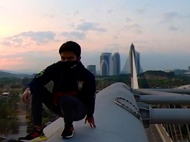 Waaghals klimt op duizelingwekkend hoge brug