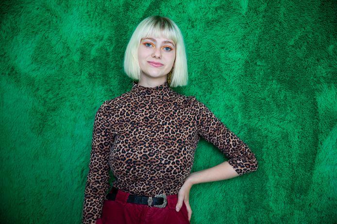 Megan Maas in haar kamer voor haar groene fluffy muur.