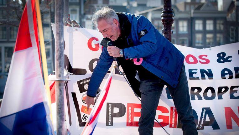 Edwin Wagensveld van de anti-islambeweging Pegida wijst tijdens een demonstratie in Amsterdam naar een hakenkruis. De gemeente Amsterdam had nazisymbolen verboden. Beeld Robin Utrecht/ANP