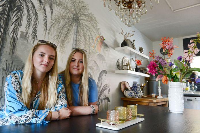 Fabienne en Valerie Valk voor de wandschildering die hun moeder Natascha heeft geschilderd. De zussen moeten de woning van moeder na haar overlijden verlaten.