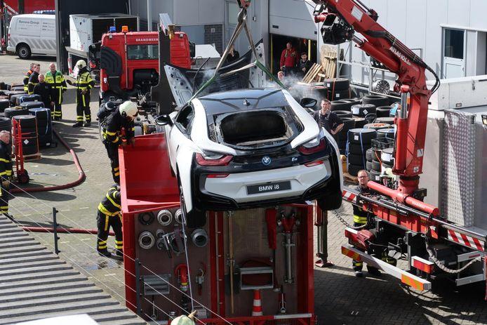 Een in Breda in brand gevlogen elektrische auto wordt in een watercontainer gedompeld om het vuur te doven.
