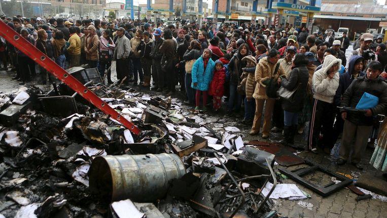 Toeschouwers kijken naar het overheidsgebouw in El Alto dat door woedende betogers in brand werd gestoken. Beeld reuters