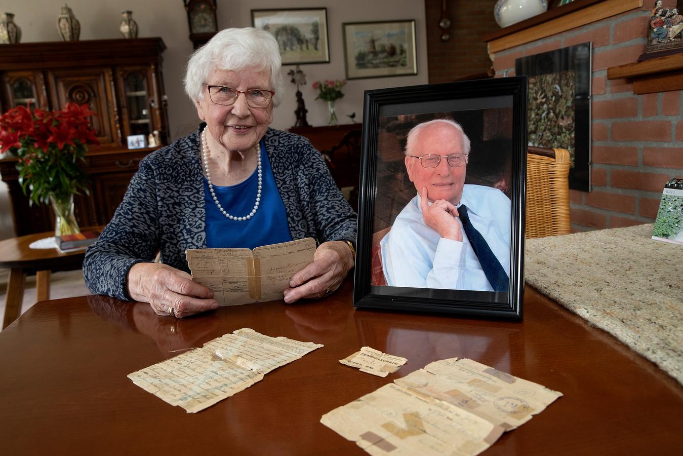 Gera de Jong-Verkerk met originele stukken van haar overleden man Ab (op de ingelijste foto) die zijn ervaringen als dwangarbeider van de nazi's op papier zette.