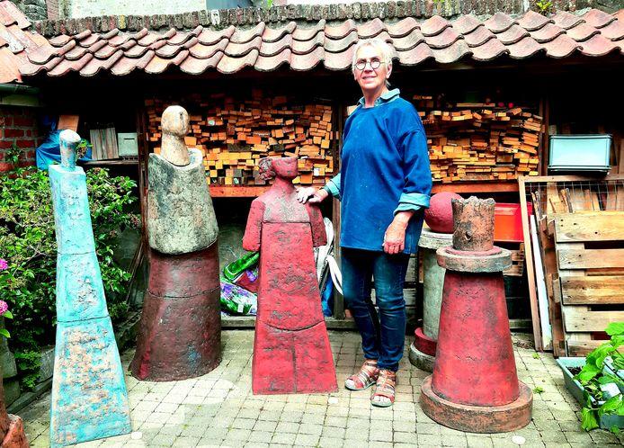 Gerdi Zwaan tussen een aantal van haar beelden.