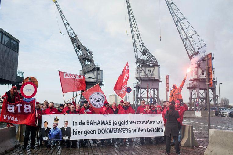 """Betogers tonen een spandoek met een tekst die Fernand Huts op de korrel neemt, de baas van Katoen Natie. """"In de Bahama's je geld verzamelen en hier geen dokwerkers willen betalen""""."""