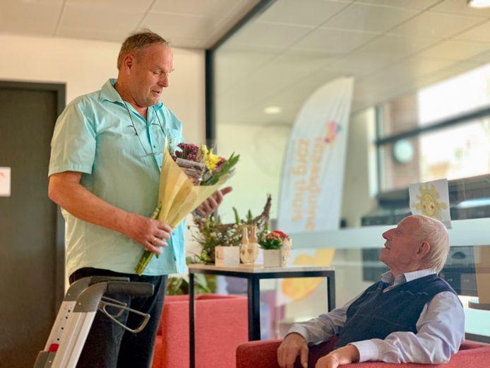 Jan van den Velden overhandigt Vita-bewoner Jan Leijten (96) een fleurige bos bloemen.