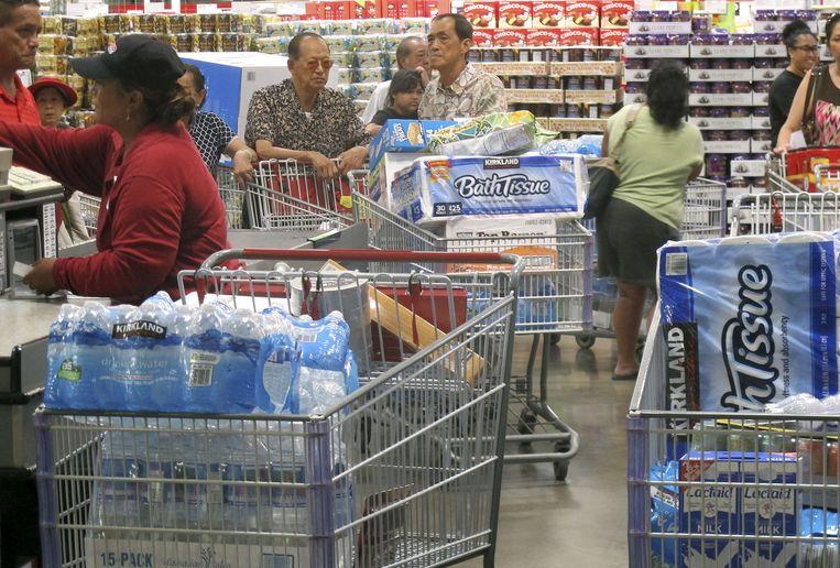 Inwoners van Hawaï staan in een lange rij voor de kassa in een supermarkt waar iedereen massaal water en wc-papier inslaat Beeld ap