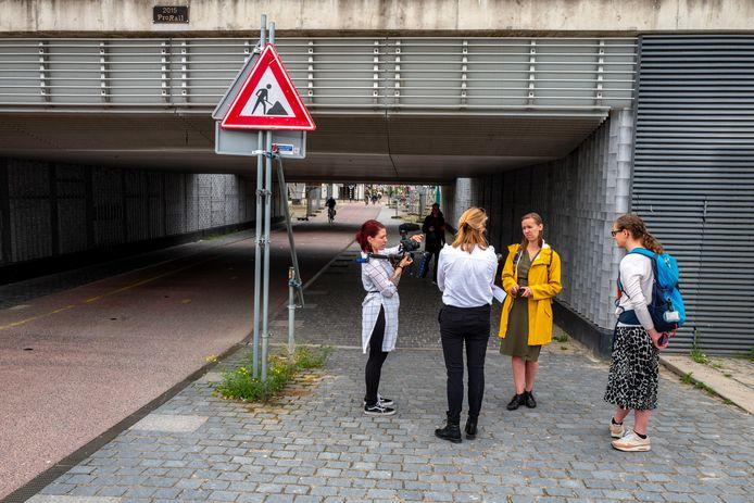 Margot (gele jas) en haar vriendin worden door medewerkers van de gemeente bevraagd over hun ervaring in de Willem II-passage.