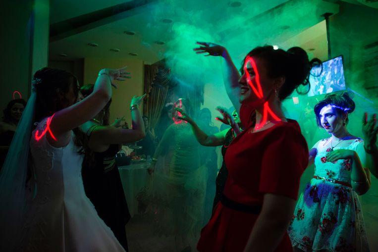 Op een huwelijksfeest in een zaal  in Teheran mogen de vrouwen alleen gescheiden van de mannen dansen. Beeld Forough Alaei