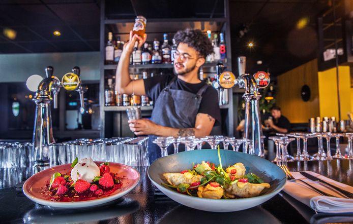 Gastro-coctailbar Annabel. Op de voorgrond links bietencarpaccio met framboos en rechts Gyoza. Op de achtergrond worden er cocktails gemaakt.