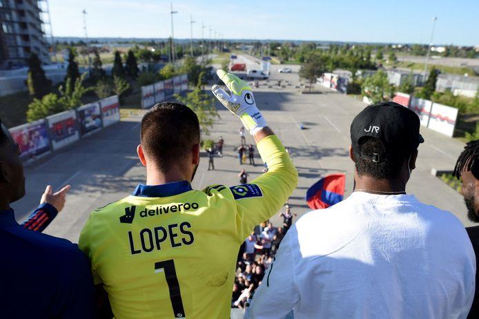 Spelers van Lyon vieren de overwinning met fans die zich buiten het stadion hebben verzameld.