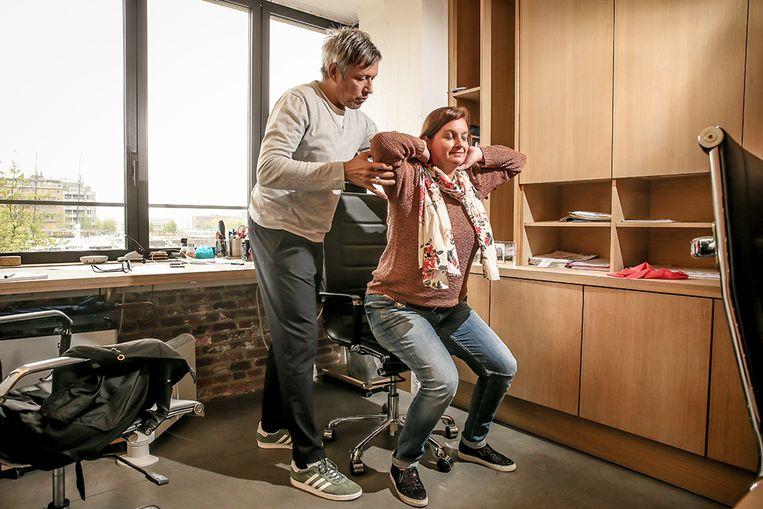 Oefening aan je bureau: Zet je voeten plat op de grond met je tenen mooi recht naar voor. Vouw je handen achter je hoofd, recht je rug, trek je schouders naar achter, sta zo op van je stoel en ga weer zitten. Beeld Pieter-Jan Vanstockstraeten / Photonews