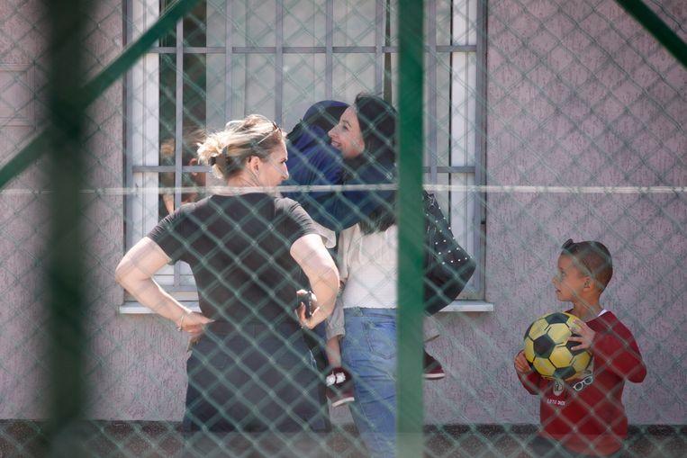 Een Kosovaarse omhelst haar zus die met kinderen terugkeerde uit Syrië en nu verblijft in een detentiecentrum in Kosovo  Beeld EPA