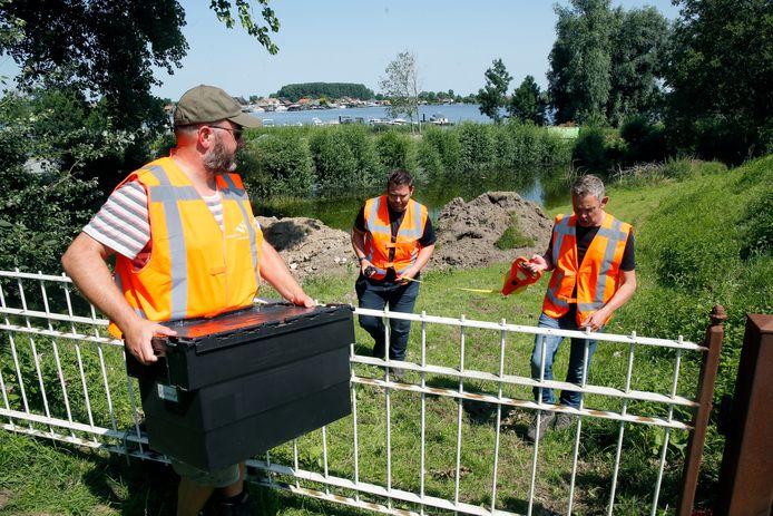 Dijkbewakers van waterschap Rivierenland komen na een controle teruggelopen uit de uiterwaarden van de Afgedamse Maas bij Andel.