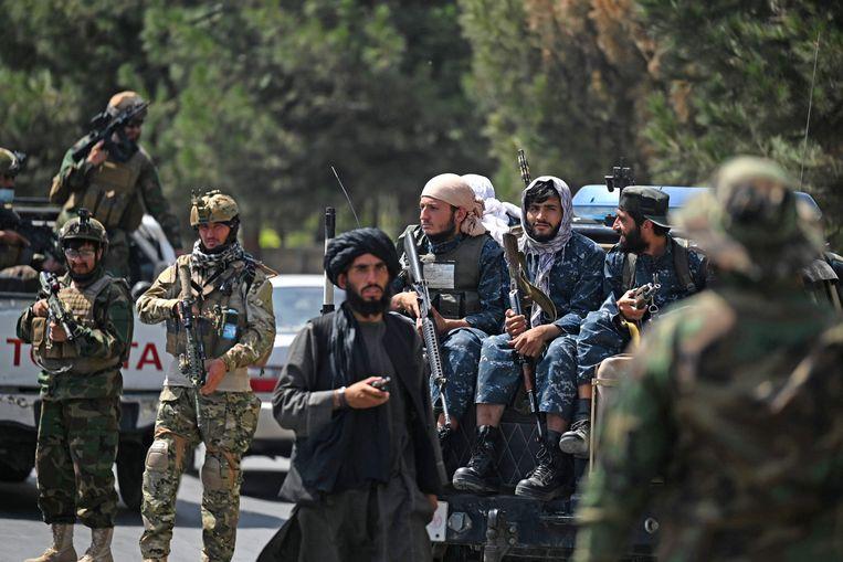 Strijders van onder meer de taliban in de straten van hoofdstad Kaboel. Beeld AFP