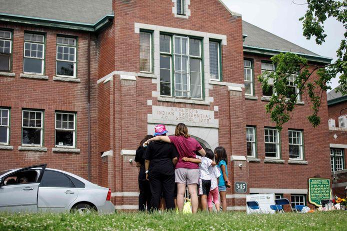 Mensen rouwen bij een van de scholen waar graven van inheemse kinderen werden gevonden.