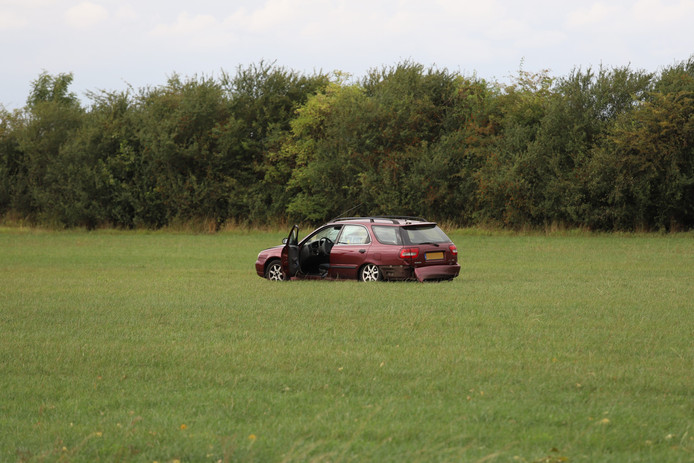 Nabij de plek van het ongeval op de Thornsestraat in persingen staat een fors beschadigde auto in een weiland.