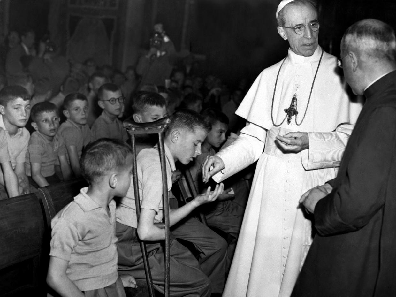 Paus Pius XII deelt hosties uit aan kinderen die in WO II verminkt zijn. Beeld AFP