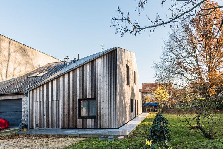 De bestaande en nieuwe gevels werden bekleed met houten latten zodat het huis visueel één geheel vormt.   Beeld MarbleMoon