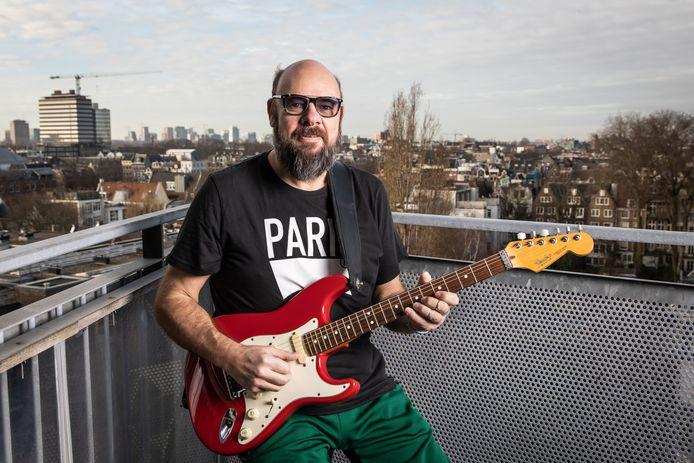 """Robert Reinders, beter bekend als Robert Jay,  op zijn balkon in Amsterdam, met zicht op theater Carré. """"Dan visualiseer ik dat ik daar straks sta, met mijn boek en gitaar in de hand."""""""