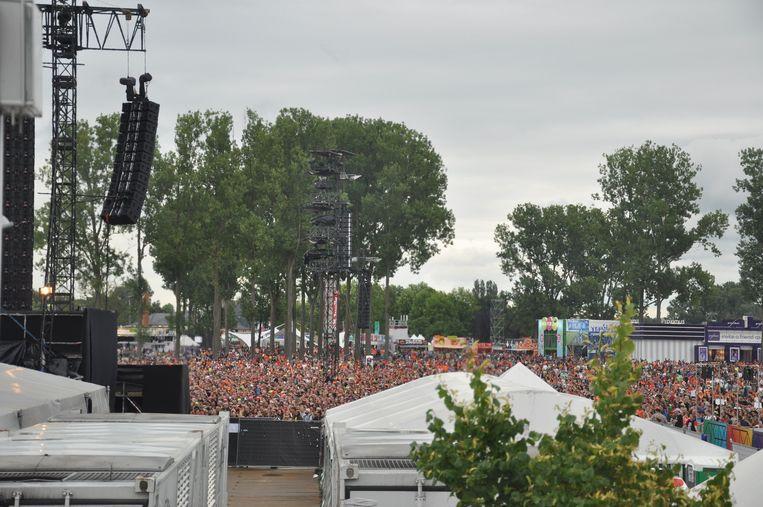 Niet enkel aan de grote schermen staat een mensenmassa, ook Triggerfinger trekt een zee van mensen. Beeld Astrid Snoeys