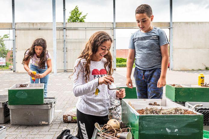 Scholieren van de klusklas werken samen aan een insectenhotel bij Karwei.  Vlnr. Alicia, Manar en Hicham