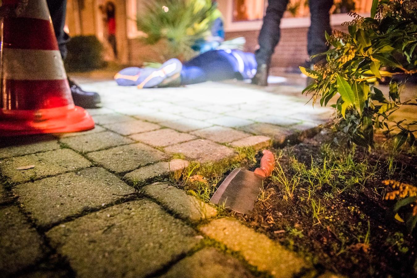 De overvaller wordt ingerekend in een voortuin in Eindhoven. Op de voorgrond het mes waarmee op de supermarktmedewerkers is ingehakt.