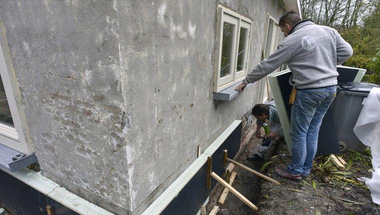 Bouwvakkers isoleren een huis. Met het energiezuinig maken van woningen kan de uitstoot van CO2 worden verminderd. Beeld Henk Brands