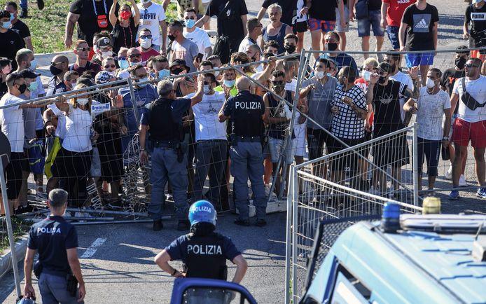 Inwoners van de stad Mondragone protesteren aan een gebouw waar 49 nieuwe gevallen van coronavirusinfectie zijn vastgesteld.