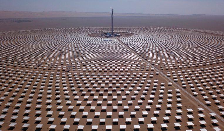 De enorme zonne-energiecentrale in de Chinese stad Dunhuang (noord-west China, provincie Gansu). 12.000 zonnepanelen weerkaatsen het licht van de zon op een indrukwekkend hoge toren, die de hitte omzet in elektriciteit.  Beeld AFP