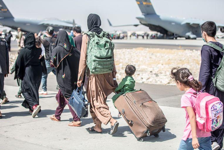 Mensen onderweg naar een vliegtuig op de luchthaven van Kaboel.  Beeld EPA