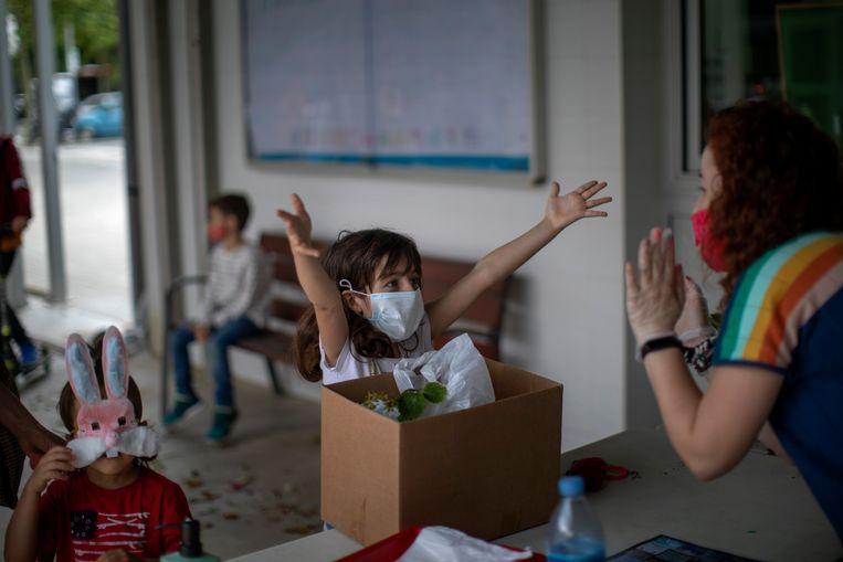Een meisje strekt haar armen uit naar haar lerares in Barcelona.  Beeld AP